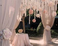 Ceremony decor with clusters of floral hanging from a chuppah with fabric--We Rent Chuppah's! love it
