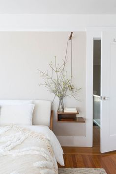 soft and inviting, minimal bedroom, neutral tones, floating side table, naked bulb, vase, bream throw