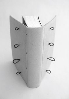 Bindings with elastic hinges  in search for the perfect opening    A regular textblock. A case made of three rigid elements, joined by elastics. When opened, the spine piece freely moves away from boards, allowing the endpaper folds to get closer to each other, thus allowing the book to fully open.