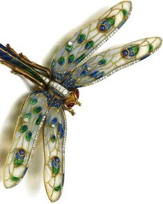 Enamel, gem set and diamond brooch Designed as a dragonfly, with blue and green enamel body and plique-á-jour enamel wings, accented with circular-cut diamonds and cabochon sapphires and rubies, one diamond deficient.