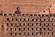 As faces do trabalho infantil na Índia. Criança indiana trabalha entre as pilhas de tijolos de uma fábrica tradicional de produção de tijolos. Na vila Bhosalewadi, estado de Maharashtra, Índia.  Fotografia: Sayid Budhi (DocBudie) no Flickr.