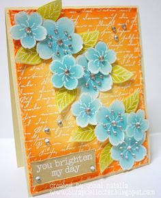 blue sakura on vellum trickle down across the card front ... script embossed in white ... yellow to orange sponged on top ...bright and  beautiful card ...