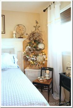 A small tree decorated with cotton boughs, a bird nest, clock faces and burlap garland.