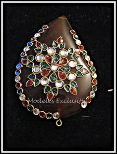 Kundan Keshri work done on a brown Agate leaf shaped pendant. Kundan keshri is a traditional form of Indian gemstone jewellery involving a gem set with gold foil between the stones and its mount, usually for elaborate necklaces. The method is believed to have originated in the royal courts of Rajasthan and Gujarat.    Leaf shaped agate pendant with Kundan work