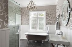 This bathroom reflects a French Country design influence – from the tub to the tongue-and-groove panelling.