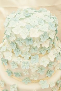 The wedding cake, decorated with blue flowers.