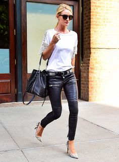 Rosie Huntington-Whiteley in a white lace t-shirt, leather skinny pants, printed heels, and a studded Saint Laurent shoulder bag