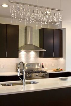 Dark wood kitchen with stainless steel appliances. Clear white tiling to top of range hood. White granite counter. Very elegant.