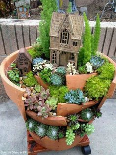 Fairy garden idea: Plants I recognize are Chicks and Hens, Dragon's Breath. Nice house on the top level.
