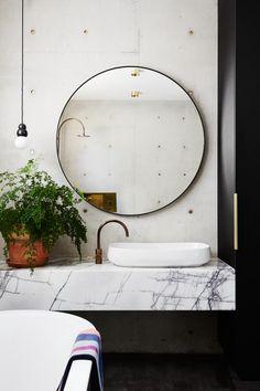 gruby, marmurowy blat pod umywalkę + okrągłe lustro w czarnej ramie
