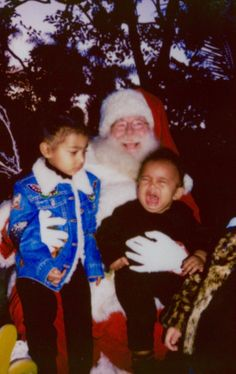 Poor baby: Saint West screams with horror as he meets Santa Claus while concerned big sister North looks on in a new picture shared by mom Kim Kardashian
