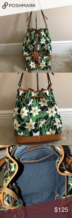 "Dooney & Bourke Drawstring Bag with Wristlet In awesome condition. Some minor flaws taken pictures of it above. Inside looks amazing. Comes with a wristlet. Color is black. Approximate measurements: Bag 12-1/2""W x 11-1/2""H x 7-1/4""D with a 12"" to 14"" strap drop; weighs approximately 1lb, 10 oz; Wristlet 8-1/4""W x 4-1/2""H x 1/4""D with a 6-1/2"" strap drop; weighs approximately 2 oz Body 81% PVC/19% cotton; trim 100% leather; lining 100% cotton Dooney & Bourke Bags Shoulder Bags"