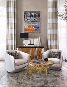 A Robert Rauschenberg artwork hangs over a Paul Evans cabinet, and a pair of Modernlink swivel chairs flank a metallic side table.