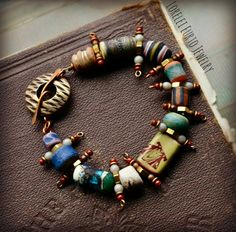 Ceramic beads- Tracey Donoughe Brass spacers- Diver Brass headpins- Vintaj Brass Co. Toggle - Thea Elements Glass rounds Seed beads Copper seed beads Measures 7.75 inches.