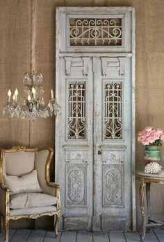 It's not often you find a salvaged door with iron accents like this one, and when you do, you display it like the work of art that it is.  door decor. interior design.  repurposed doors, refurbished doors, recycled design.  old doors.  vintage doors.