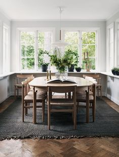organic modern dining room with white walls, warm wood floors, dark charcoal rug, and plants