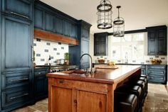 Kitchen. Rustic Kitchen with Navy Blue Cabinets. Rustic kitchen with navy blue cabinets. The hand-crafted island, topped with an 11-foot cut of distressed cherrywood, seats five and functions as the chef's table for the husband, an avid cook. The perimeter cabinetry is cherrywood painted Mozart Blue by Benjamin Moore with black glaze. #BenjaminMooreMozartBlue #Kitchen #Cabinet #PaintColor #BlueKitchen #NavyKitchen Heidi Piron Design.