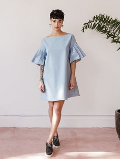 Woven boatneck shirt dress with elbow length pleated kimono sleeves. Dress comes with self fabric belt. - Available in light blue denim or white cotton shirting - Light Blue Denim: 97% Cotton 3% Elastane - White Poplin Shirting: 100% Cotton - Hand wash cold, line dry. For best care dry clean - Boxy fit. Size small measures 39 at bust and 35 in length - Made in Seattle, WA