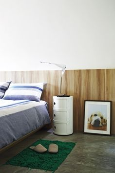 In the compact master bedroom, a wood-grain feature panel serves as a headboard, while the Leaf lamp by Yves Behar provides sculptural interest.