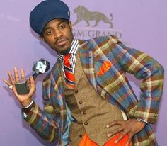 """Andre 3000: Proving the Fashion Law of Black Men, which states that a Black man can pull off any fashion choice if he has a confident look on his face. Andre's outfit combines patterns and colors at a swaggering volume. The boldness of the copper is offset by the softness of the blue. Checkered shirt mixes with plaid jacket and boldly striped tie, however the solid pants and hat to keep it all from escaping and frightening the children."""
