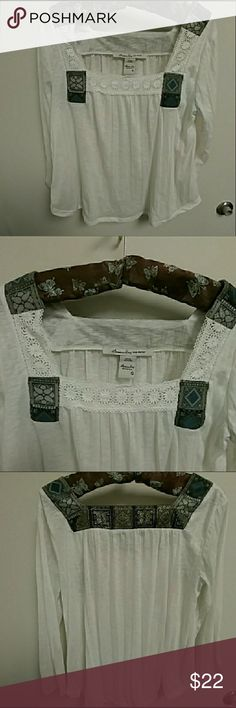 American Rag white lacy peasant style blouse This super cute & trendy long-sleeve cotton blouse by American Rag features a Byzantine-inspired print & lace trimmed squared neckline. The blouse is in a heathered white with a rounded shirt-tail hem. 100% poly. In excellent used condition (no rips, tears, or stains.) American Rag Tops Blouses