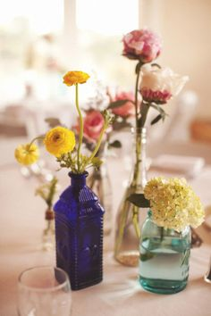 Assorted bottles with a variety of flowers combine to make a lovely graduation party tablescape.