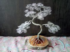 Handmade wire tree on a 12 cm tree trunk base. The height of the tree is 24cm wide by 23cm wide.