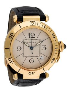 Men's 18K yellow gold 39mm Cartier Pasha de Cartier Watch featuring engraved bezel, flat creme dial, Arabic and index hour markers, date aperture, luminous sword hands, push/pull fluted crown with spinel accented cover, black alligator strap and 18K yellow gold deployant closure.