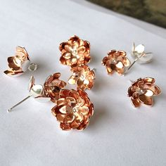 At the jewellery bench | Tulip pendants and earrings in copper and silver.