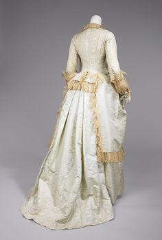 Moiré silk tea gown with cotton lace trim (back), probably American, 1875-80. The teagown was intended to be worn at home while greeting receiving people. It did not require the wearer to don a corset underneath. This level of comfort was only permissible in one's own home. An interesting construction aspect of this teagown is the back, which resembles a redingote and adds a masculine touch to a highly feminine garment.