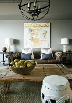 Black metal light fixture; gray walls; white pillows, lamps, and stool; brown couch and bowl; beige table and rug; green moss balls; dusty-blue pillows. Im also discovering I like the dark brown leather couch combined with a rustic coffee table look. color-themes