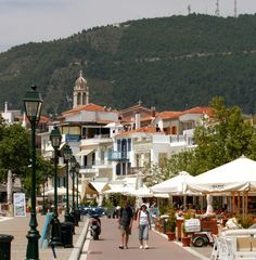 Tourists walking by a streetside cafe in the Old Port of Skiathos town
