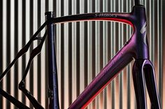 Drawing inspiration from the paint scheme of a limited edition Aston Martin the S-Build S-Works Roubaix Disc Frameset in Amphibian Blue is effortlessly classy and visually striking. A still image does not do justice to the color shift that occurs when you view this frame from different anglesfrom purple to blue to gold. The Rocket Red a mainstay of Specializeds pain schemes over the years is vibrant and speedy but is strategically placed so as to not overwhelm the blue. Subtle and refined…