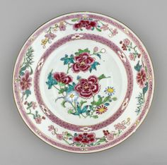 A Chinese famille rose porcelain plate painted at the centre w 3 peonies & blue & red flowers; well border of pink diaper ground & 6 white flowerheads. Rim of 4 floral sprays (alternating camellia & prunus & pink).