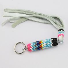 Carry your keys around in style! Navajo artist Charlene Jackson hand beaded this beautiful key ring. Great colors and patterns. 9 3/8″ x 5/8″ x 5/8″ Artist card included