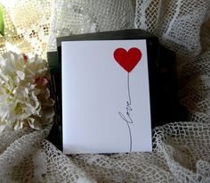 Simple Script love is hand stamped in black ink on whisper white card stock, with an embossed dotted swiss red heart. Simple and sweet. While I