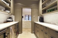 Gray butler's pantry features gray shelving over gray cabinets topped with white marble countertop and white marble backsplash.