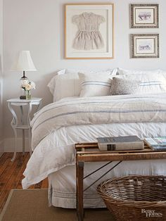 Piled with natural linens, this cottage bed gets a boost from a framed child's dress above the headboard. Soft neutrals carry throughout for a relaxed rustic look, while natural fabrics and materials contribute snug texture./