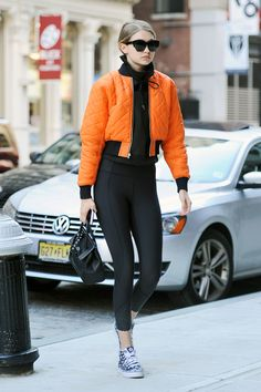 Gigi Hadid out in NYC wearing an orange bomber jacket with black leggings and printed sneakers. Gigi Hadid Looks, Gigi Hadid Style, Athleisure, Orange Bomber Jacket, Estilo Gigi Hadid, Gigi Hadid Outfits, Cute Spring Outfits, Sporty Outfits, Cropped Hoodie