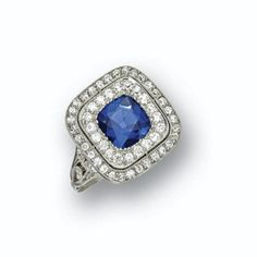 SAPPHIRE AND DIAMOND RING, CIRCA 1915 The cushion-shaped sapphire measuring approximately 7.50 by 7.50 by 4.51, framed by a double row of round diamonds weighing approximately 1.00 carat, mounted in platinum