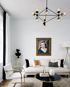 You need to see Havenly Head of Design Shelby Girard's black and white chic, modern home makeover—we love the plush white couch, moroccan rug, midcentury modern Moto chandelier and gold accents in this gorgeous sitting room! Click to see more of this beautiful space.