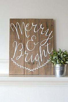 """Reclaimed Wood Art Sign: Merry & Bright Christmas Holiday Home Decor. Celebrate the Christmas season with this unique sign! This original painting was created on old shipping pallet pieces. The wood was disassembled, cut, sanded and reassembled. It was then stained in a muted grey/brown acrylic wash. The words """"Merry & Bright"""" were then hand sketched and painted in white acrylic. Boxwood strands were then hand sketched and painted in white acrylic. This painting comes with installed eye…"""