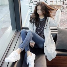 Black printed shirt with a white cardigan and skinny jeans and white sneakers