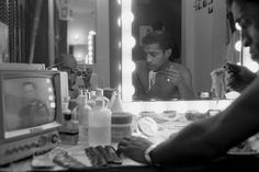 """<strong>Not published in LIFE.</strong> Sammy Davis Jr. eats spaghetti in his <i>Golden Boy</i> dressing room while watching <i>The Huntley-Brinkley Report</i> news show in 1964. """"My only contact with reality,"""" he told LIFE. """"Whatever I'm doing, I stop to watch these guys."""" Reflected in the mirror: LIFE photographer Leonard McCombe."""