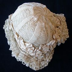 A wonderful bonnet almost entirely covered in Valencienne lace and ribbons. The ornate crown on the bonnet has two layer of lace, with masses of ribbon rushing around the edges of the bonnet.