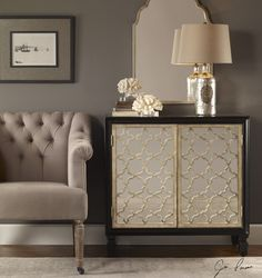 This console cabinet features gloss black wooden case with an interior shelf, featuring mirrored doors inset with an intricately-cut quatrefoil lattice in burnished silver leaf. Click image for greater details.  Item measures34 W X 32 H X 14 D (in)