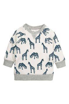 Sweater met print: Een sweater van joggingstof met een print en een geruwde binnenkant. De sweater heeft lange raglanmouwen, drukknopen in de nek en een ribboord aan de onderkant en onder aan de mouwen.
