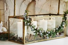 .candles and greenery in vintage glass case
