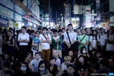 CHINA, HONG KONG : People listen to long-awaited talks between student leaders and senior government officials being broadcasted live at a protest site in the Mongkok district of Hong Kong on October 21, 2014. Hong Kong's embattled leader on October 21 said he was open to creating a more democratic election committee before elections in 2017, extending a potential olive branch to democracy protesters as crunch talks to end the demonstrations got underway. AFP PHOTO / Philippe Lopez