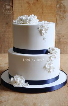 White Roses & Blossoms on a White cake with Navy Blue Ribbon.  Wedding Cake - iced by kez #weddingcake #whiteandnavywedding